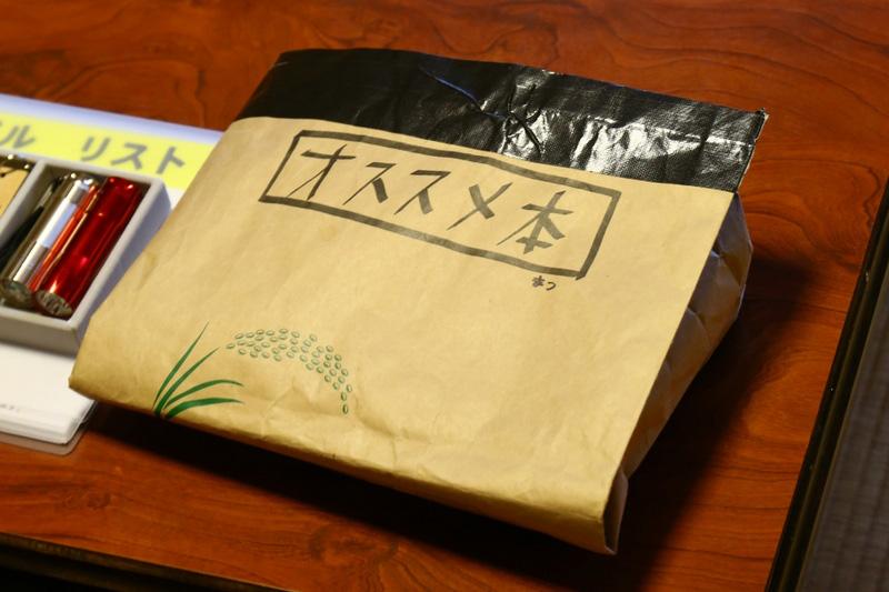 部屋の机の上にはd design Travel 山梨号のほか、高村さんオススメ本が入った袋が置かれている